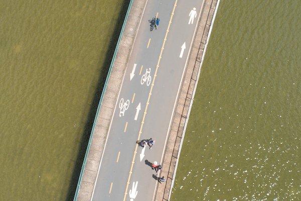 Ciclistas pedalam por ciclovia no Parque da Cidade
