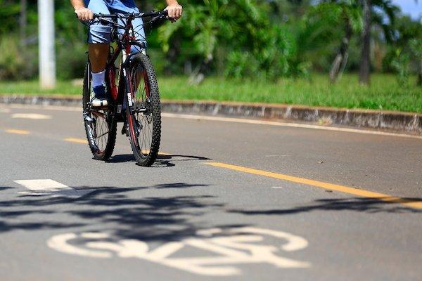 Ciclista pedala por ciclovia no Parque da Cidade