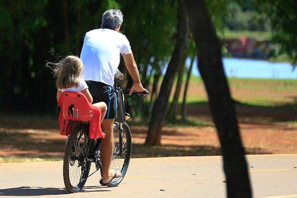 Pai e filha andam de bicicleta no Parque da Cidade
