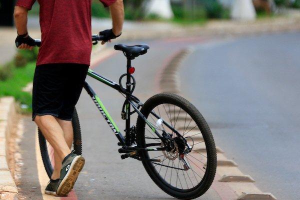 Homem com bicicleta em ciclovia de Águas Claras