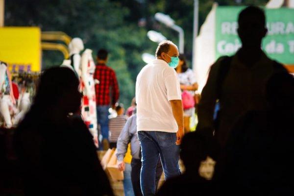 Homem de camisa branca usa máscara na rua contra o coronavírus