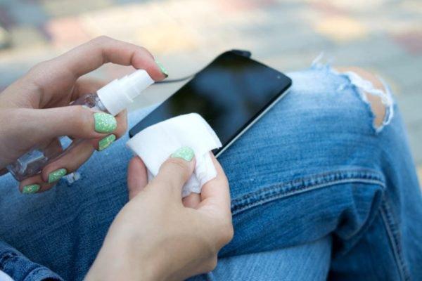 Mão feminina segurando celular e limpando