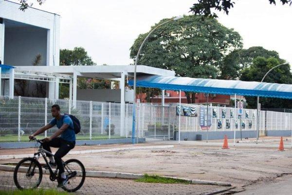 jovem anda de bicicleta em frente a colégio fechado na Asa Sul
