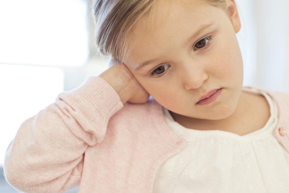 Criança com a mão no ouvido