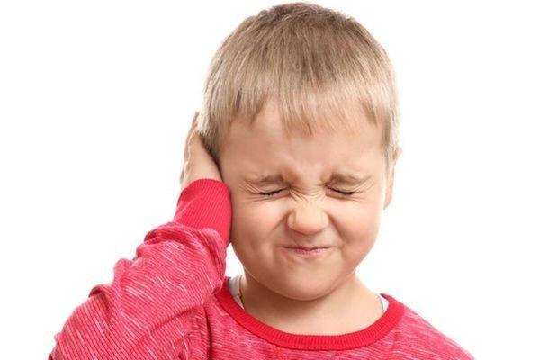 Menino loiro de camiseta vermelha com as mãos no ouvido, fazendo careta