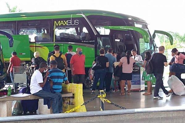 Passageiros aguardam para embarcar em frente a ônibus verde