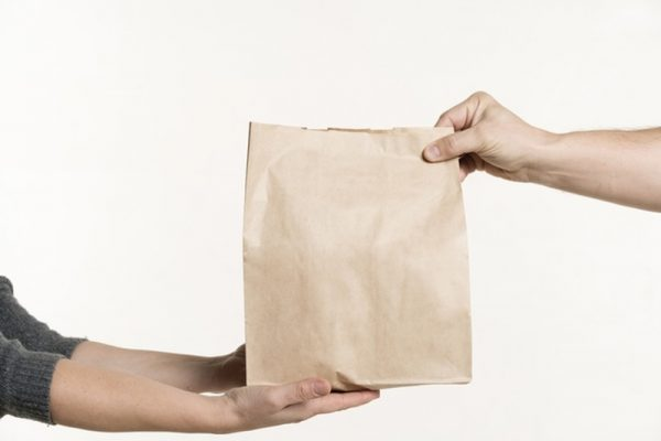Vista frontal de mãos segurando um saco de papel