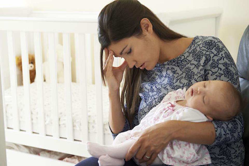 Mulher segura bebê de colo com expressão de cansaço