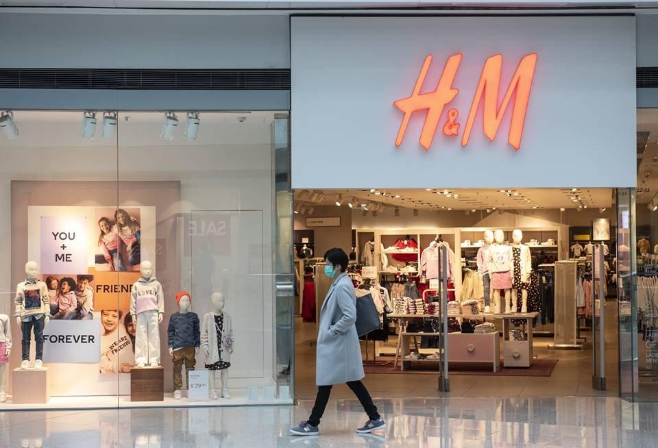 Mulher passando de máscara cirúrgica na frente de uma loja da H&M