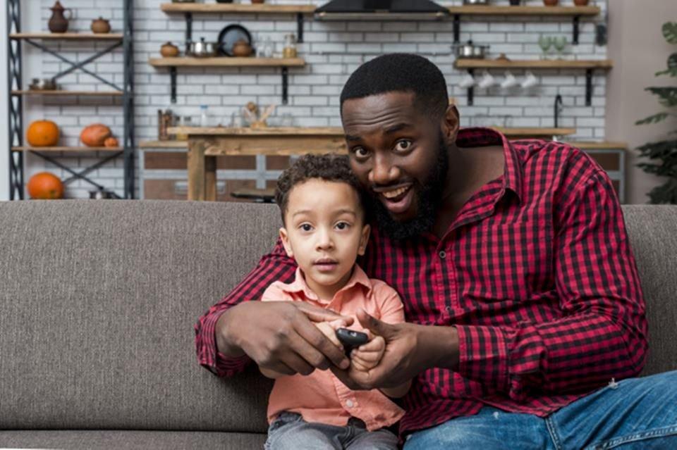 Homem negro e filho assistindo tv