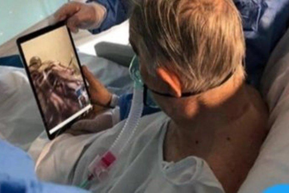 Homem acamado olhando tablet
