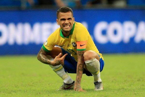 Dani Alves agachado com a camisa do Brasil