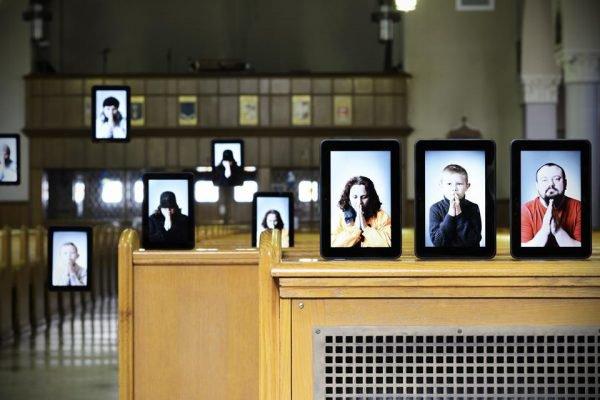 Cenário de igreja com vários tablets em que fieis aparecem orando