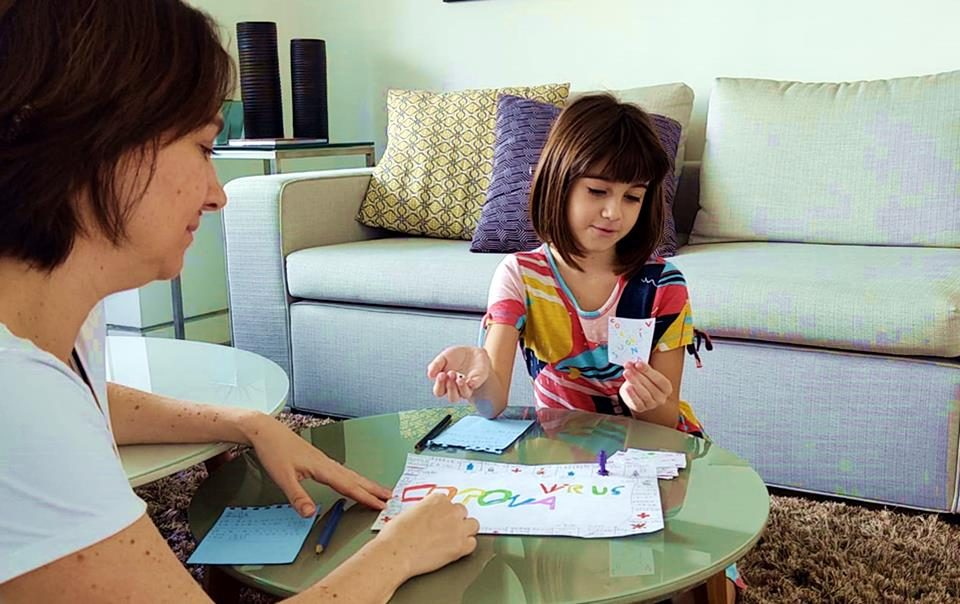 Menina brinca de jogo de tabuleiro do coronavírus com a mãe