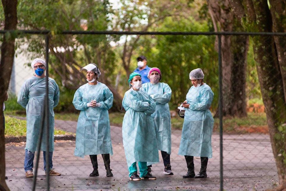 Enfermeiros em pé e de braços cruzados