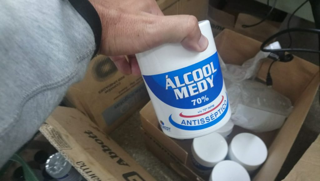 Policial segura frasco branco com inscrição álcool medy