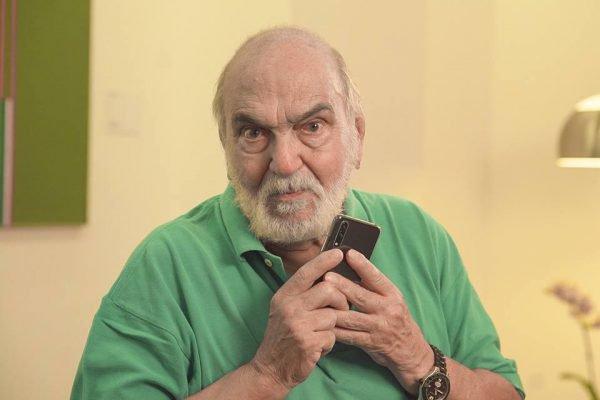 Lima Duarte com celular e blusa verde