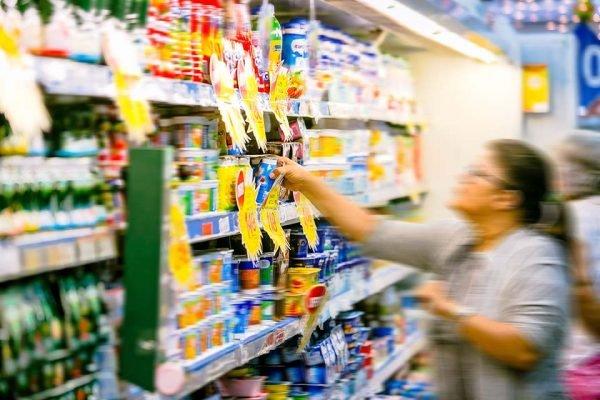 mulher faz escolhe de produtos em pratilheira de supermercados