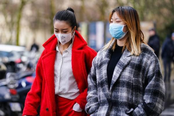 mulheres usando máscara descartável na rua por causa do coronavírus