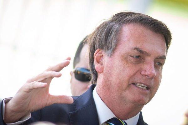 Jair Bolsonaro e homem de óculos atrás