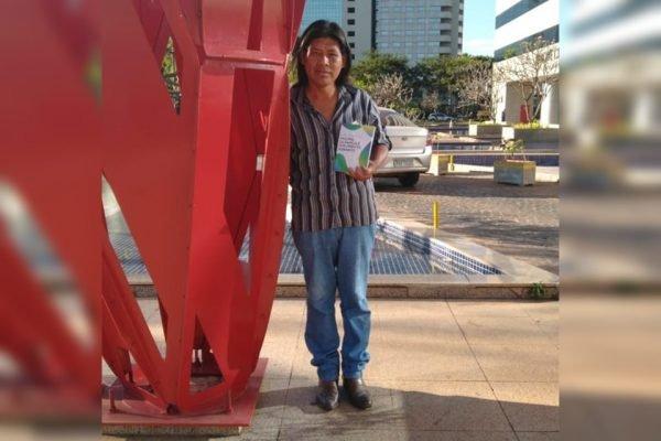 Homem ao lado de escultura segurando livro
