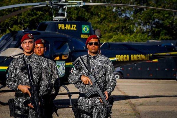 Soldados da força nacional com helicoptero ao fundo