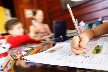 Aluna faz lição de casa junto com a familia