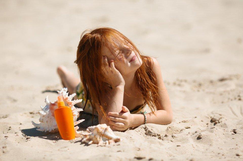 Menina ruiva tomando sol
