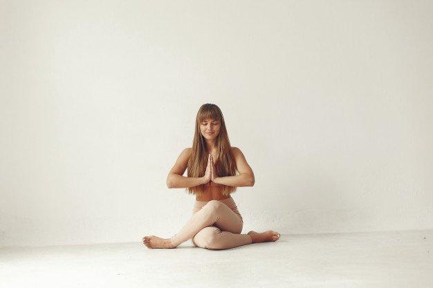 Mulher branca de cabelos lisos vestidas em roupas de tons nudes praticando yoga