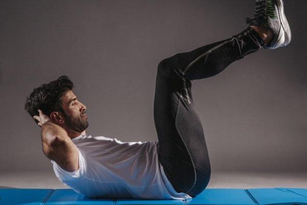 Homem deitado no chão fazendo abdominais