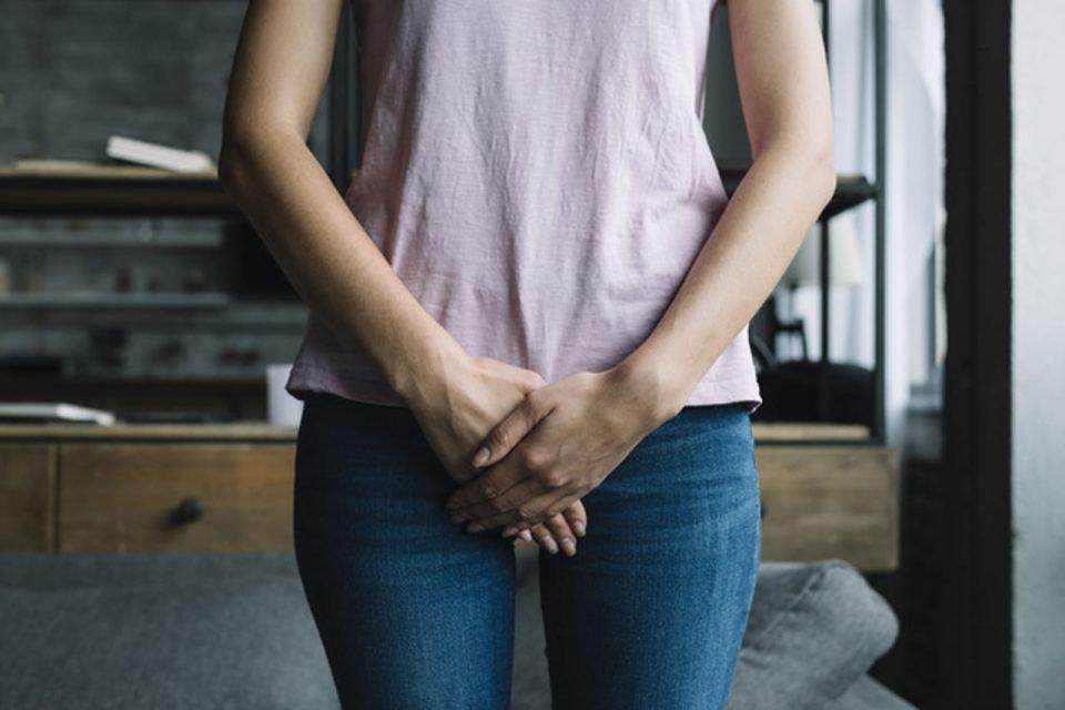 Mulher com as duas mãos em frente ao órgão sexual