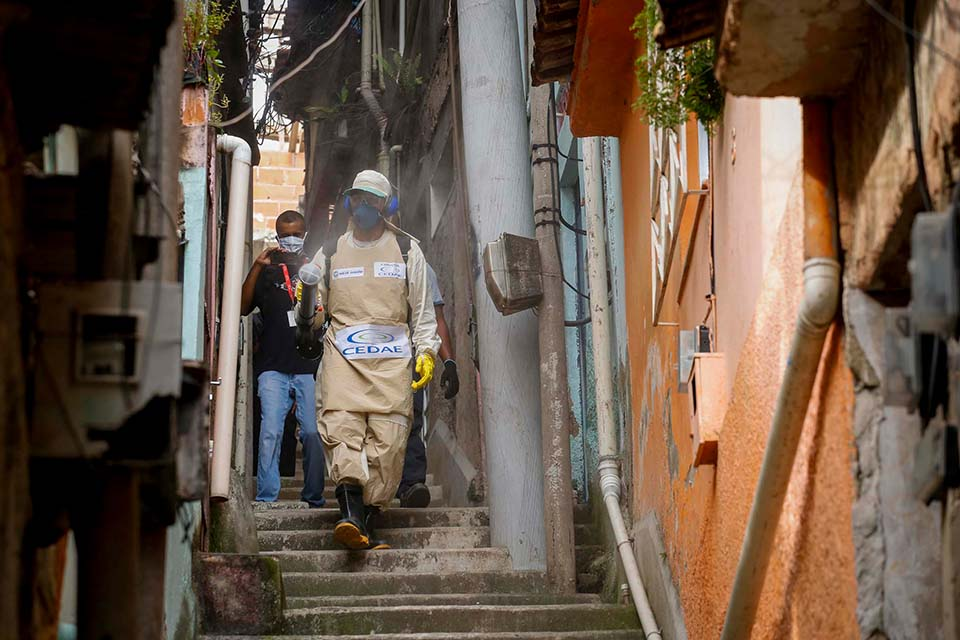 Homem usando roupas especiais faz a limpeza de uma favela do rio de janeiro