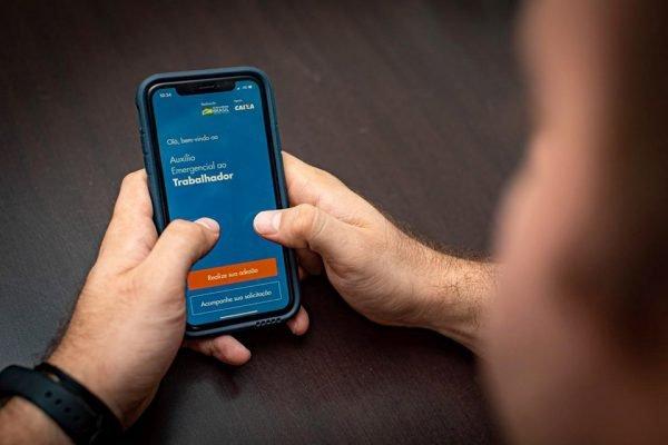 Homem utiliza aplicativo app de auxilio do governo contra a falta empregos pelo covid19