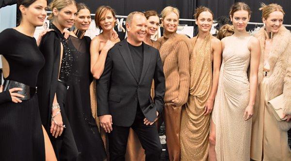 Michael Kors cercado por modelos