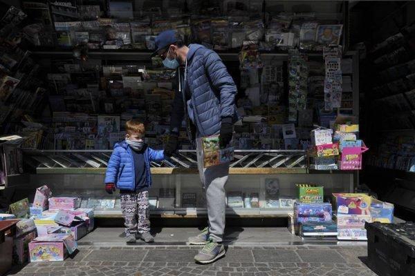 Pai e filho em livraria na Itália durante pandemia do coronavírus