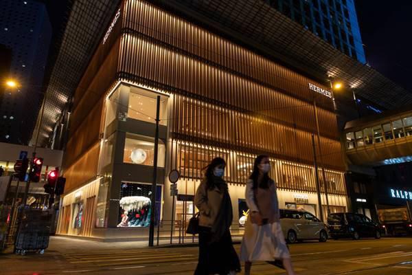 loja Hermès com pedestres de máscara