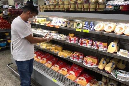 Homem escolhe produto no supermercado
