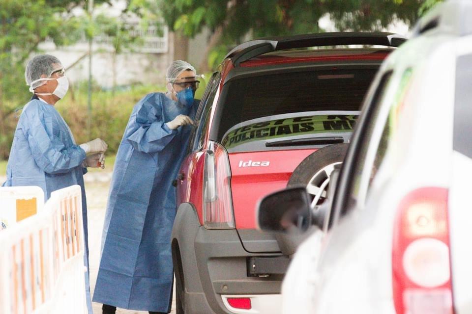 Profissionais da Saúde de máscaras e ao lado de um carro vermelho