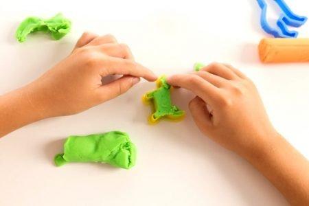 Mão de criança brincando com massinha de modelar