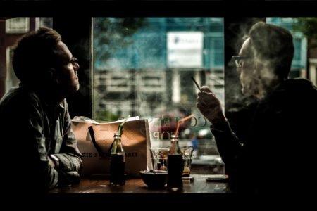 Homens fumam em ambiente fechado