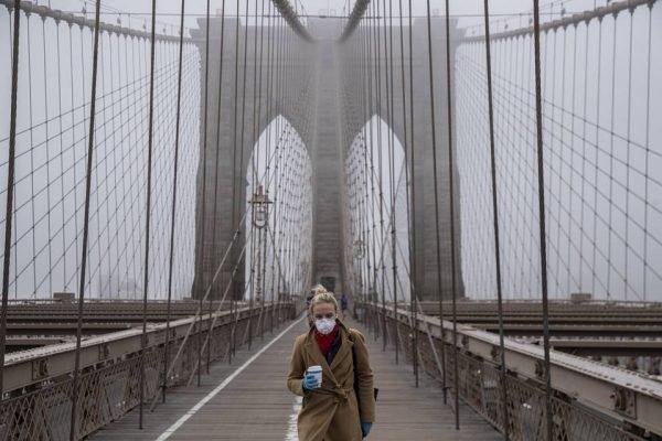 Mulher caminha de máscara na Brooklyn Bridge em Nova York em meio à pandemia do novo coronavírus (Covid-19)