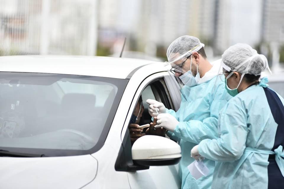 Profissionais da saúde aplicam teste rápido de coronavirus em paciente dentro do carro