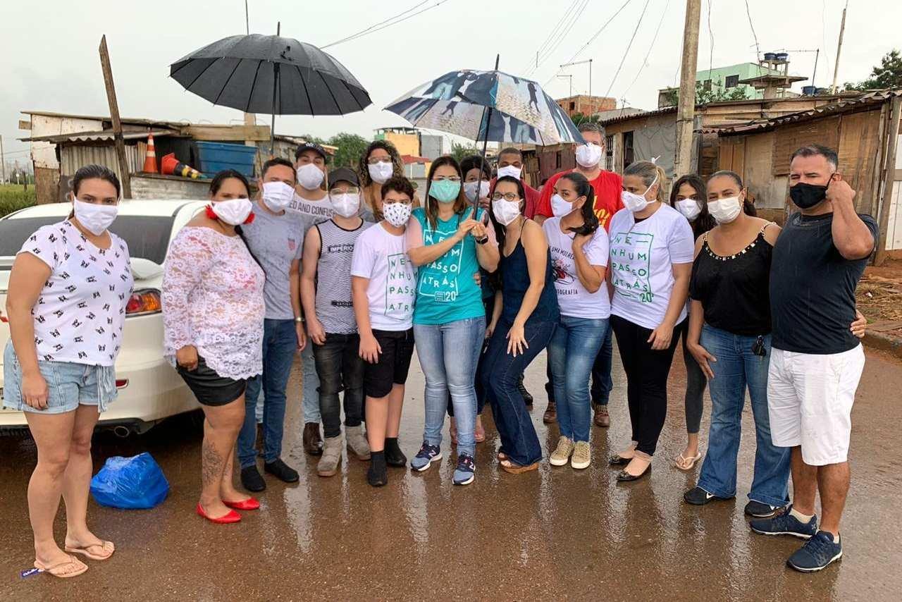 Pessoas com máscara entregam doações