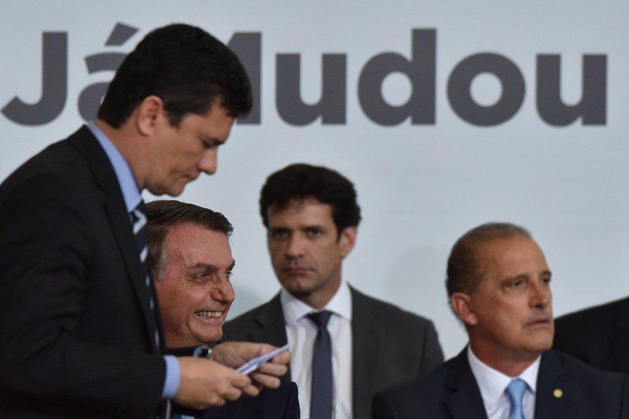 """Moro e Bolsonaro em frente a cartaz """"já mudou"""""""