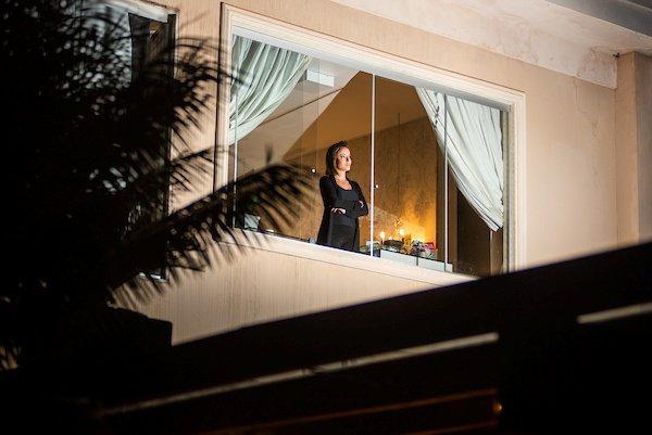 Mulher com os braços cruzados com janela aberta