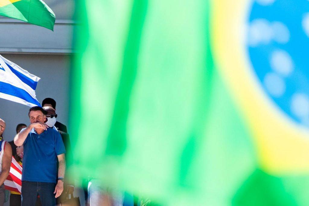 Bolsonaro coloca a mao no rosto durante protesto em brasilia