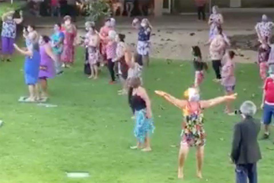 Grupo de idosos dançam em gramado