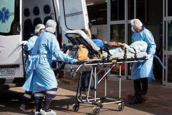 Paciente em maca e profissionais de saúde