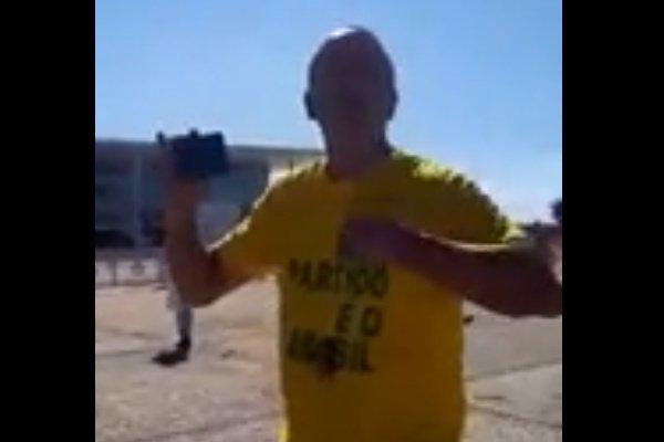 Homem de camisa amarela e celular na mão