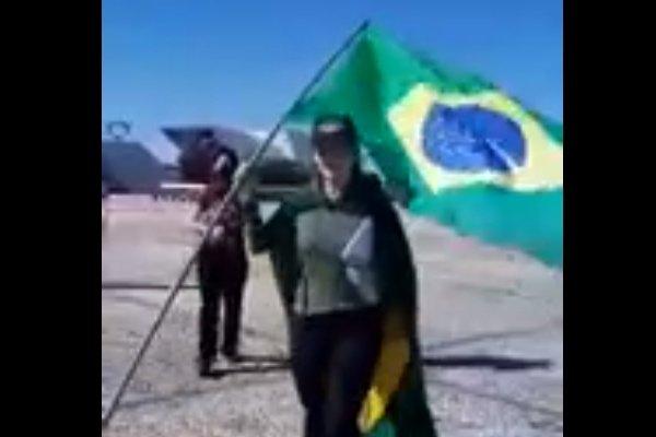 Mulher de boné e bandeira do Brasil na mão
